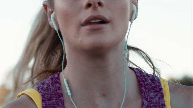 woman jogging in urban setting - headphones stock videos & royalty-free footage