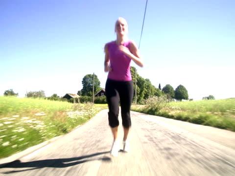 vídeos y material grabado en eventos de stock de a woman jogging next to a corn field sweden. - una mujer de mediana edad solamente