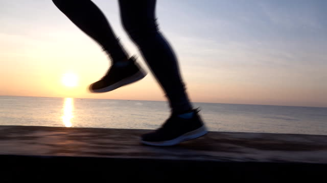 slo mo woman jogging on a promenade along the sea - human leg stock videos & royalty-free footage