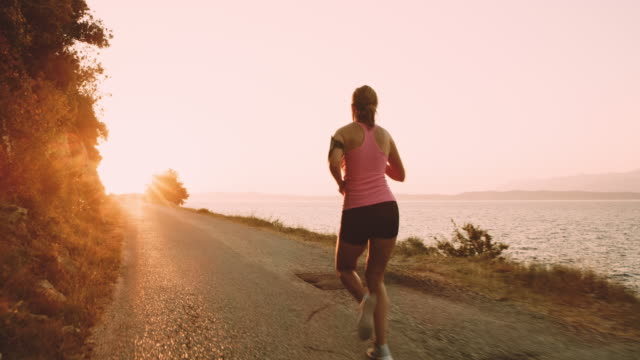 slo mo woman jogging on a road along the sea - running stock videos & royalty-free footage