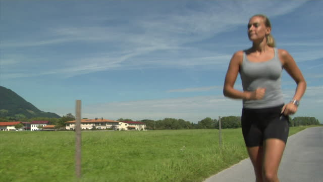 ms la woman jogging on country road, bavaria, germany - approaching stock videos & royalty-free footage