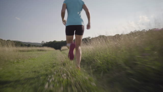 4K woman jogging on meadow betweeh high grass back view