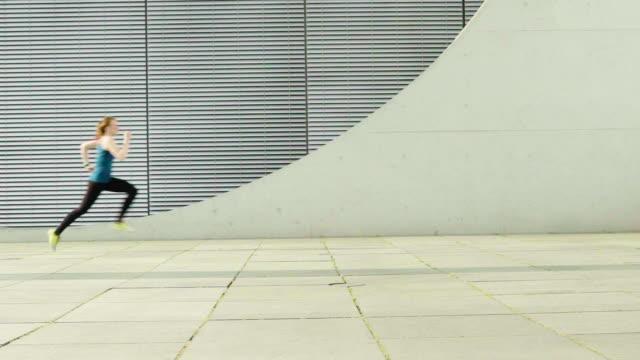 vídeos de stock e filmes b-roll de woman jogging on sidewalk against building in city - vista lateral