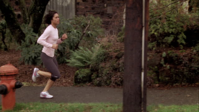 vídeos de stock e filmes b-roll de ws ts woman jogging on sidewalk / portland, or, usa - plano geral