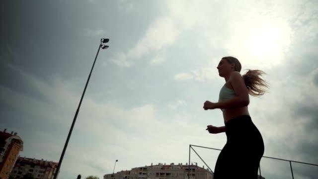 vídeos de stock, filmes e b-roll de mulher correndo na pista de corrida - low angle view