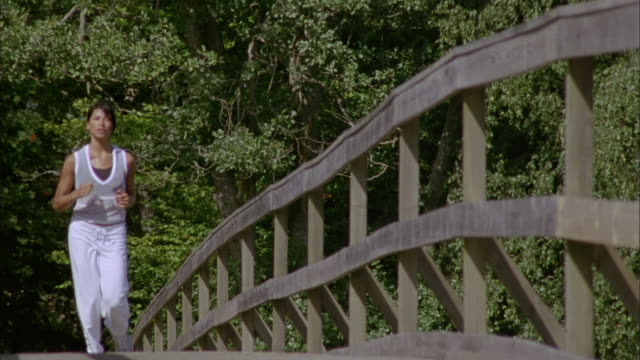 slo mo ms pan woman jogging on wooden footbridge, ryd, smaland, sweden - ノースリーブトップ点の映像素材/bロール
