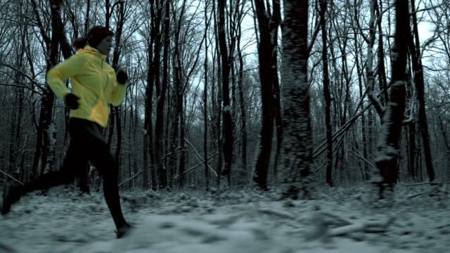WS Woman jogging through a forest in winter