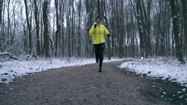 WS Woman jogging through a winter forest