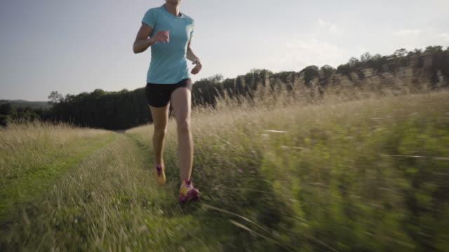 4K woman jogging through high grass in summer