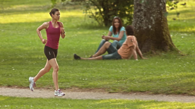 SLO MO TS Woman jogging through the park