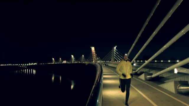 SLO MO Woman jogging with a headlamp on across the bridge