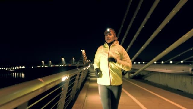 vidéos et rushes de slo mo femme jogging avec un projecteur sur - lampe frontale