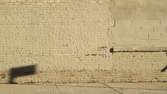 vidéos et rushes de a woman jogs beside a brick wall casting her shadow over its surface. - mur brique