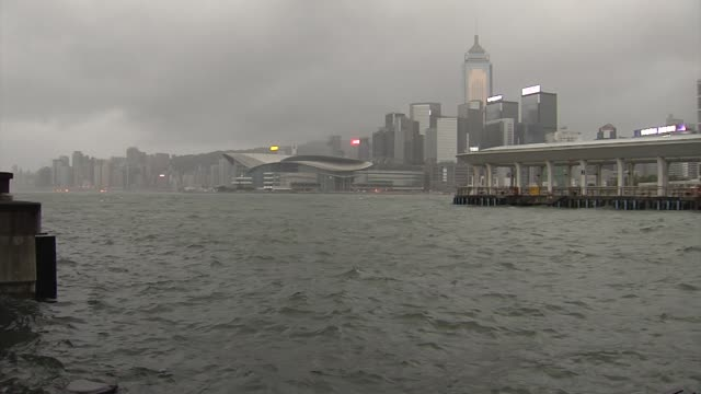 a woman jogs near a pier by the waterfront during a no 10 hurricane signal raised for typhoon hato in hong kong china on wednesday aug 23 storm... - central plaza hong kong stock videos & royalty-free footage