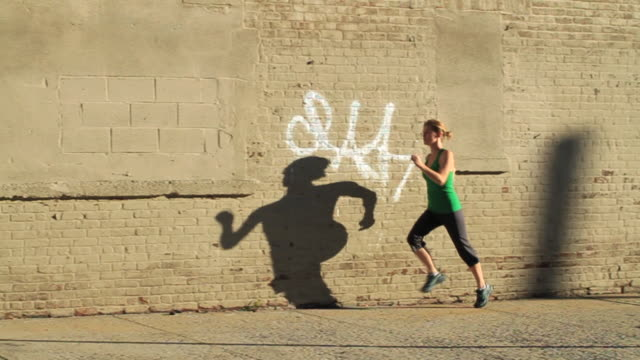 A woman jogs past graffiti on a brick wall casting her shadow along its surface.