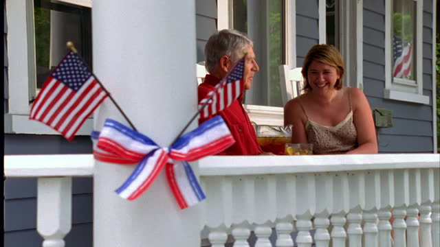 a woman joins an elderly man sitting in a rocking chair on a porch decorated with american flags. - porch stock videos & royalty-free footage