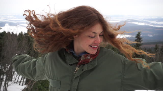 Woman joyfully jumping around in landscape in slow motion