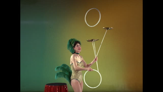 woman juggles hoops and spins plates - jonglieren stock-videos und b-roll-filmmaterial