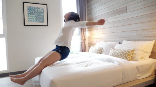 woman jump on the bed and relaxing in the room at holiday time - bedroom stock videos & royalty-free footage