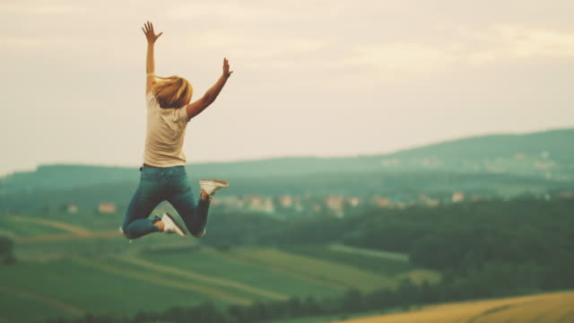 MS Woman jumping for joy in rural field