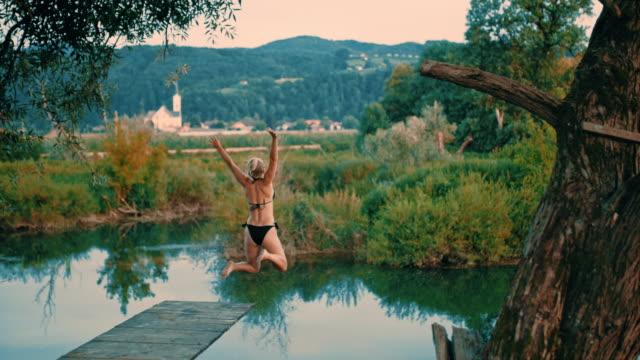 super slo mo frau springt von einem sprungbrett - swimwear stock-videos und b-roll-filmmaterial