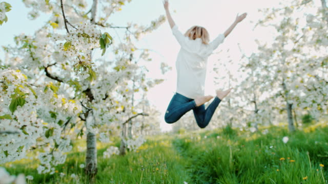 SLO MO Woman jumping in joy among cherry blossoms