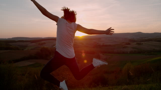 slo mo woman jumping in joy at sunset - arms raised stock videos & royalty-free footage