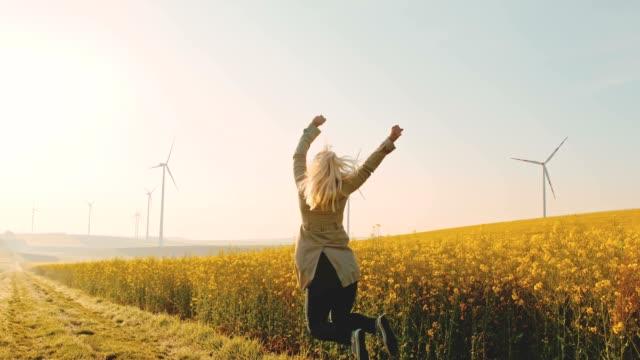 slo mo frau springt vor freude neben einem rapsfeld mit windkraftanlagen in der ferne - erneuerbarkeit stock-videos und b-roll-filmmaterial