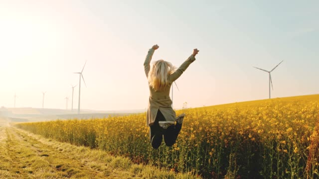 vídeos de stock e filmes b-roll de super slo mo - time warp effect woman jumping in joy next to a canola field with wind turbines in the distance - joy