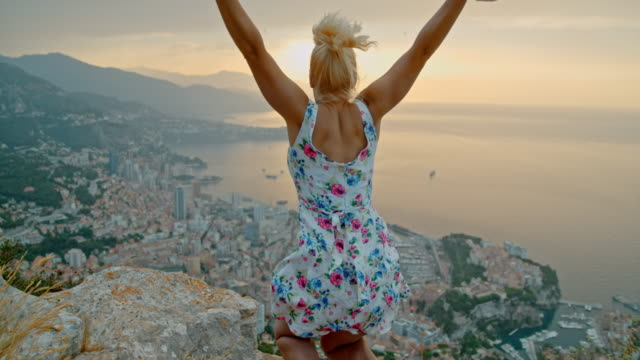 vídeos de stock e filmes b-roll de slo mo woman jumping in joy on a rock above the monaco - time warp effect - rocha