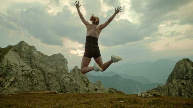 vídeos de stock e filmes b-roll de slo mo woman jumping in joy - roupa desportiva