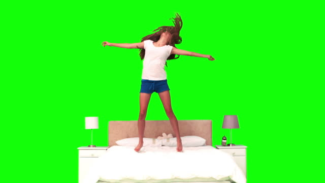vídeos de stock, filmes e b-roll de woman jumping on her bed in slow motion - barefoot