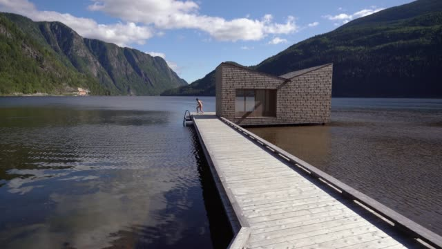 woman jumping into the lake after sauna  in norway - wood material stock videos & royalty-free footage