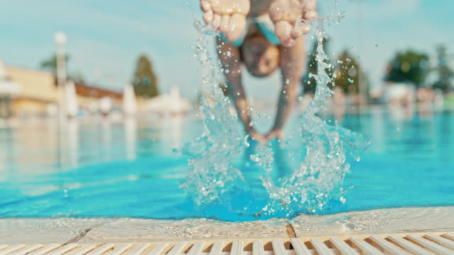 super slo mo woman jumping into the pool from a poolside - poolside stock videos & royalty-free footage