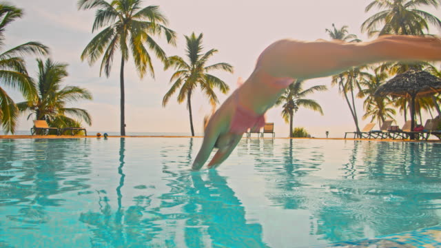 slo mo woman jumping into the pool of a luxury beach resort - swimming pool stock videos & royalty-free footage