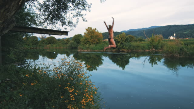 slo mo woman jumping into the river - standing water stock videos & royalty-free footage
