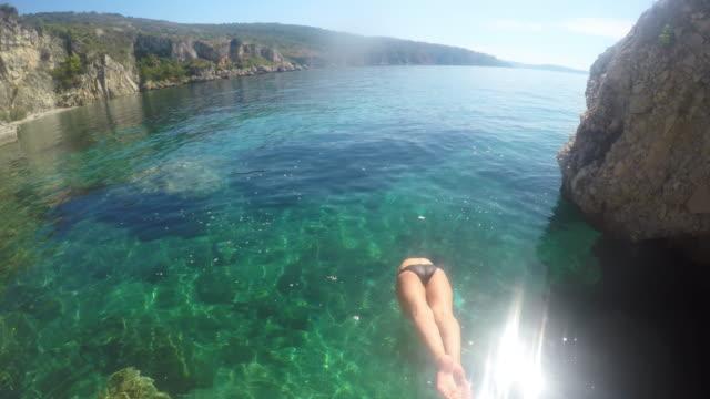 vidéos et rushes de ws femme sautant dans la mer d'un rocher - maillot de bain femme