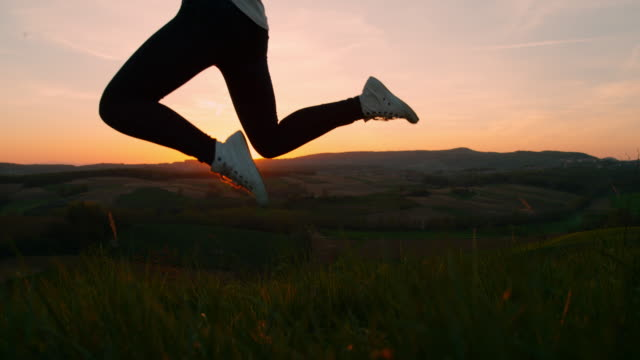 vídeos de stock e filmes b-roll de slo mo woman jumping on a hill at sunset - membro humano