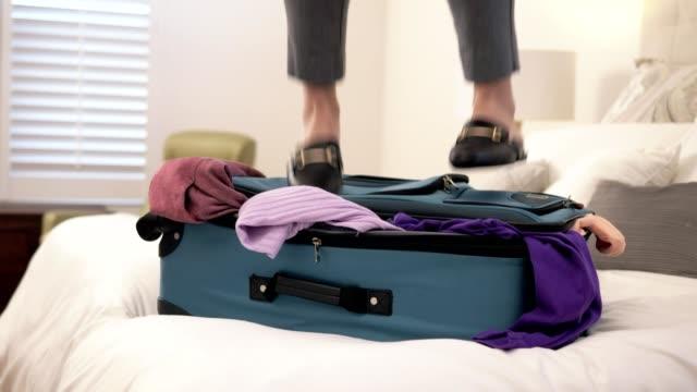 kvinna hoppa på överfyllt resväska. - packa bildbanksvideor och videomaterial från bakom kulisserna
