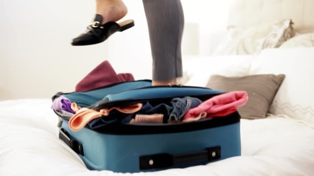 Woman jumping on overfilled suitcase.