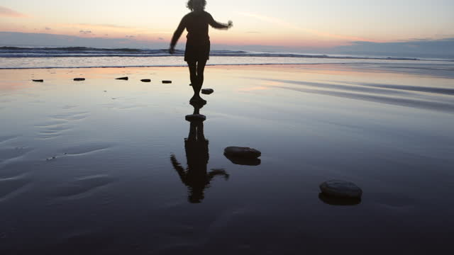 woman jumping over stepping stones at sunset - balance stock videos & royalty-free footage