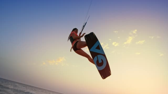 slo mo woman jumping with her kiteboard, doing a grab and smiling at sunset - kiteboarding stock videos & royalty-free footage