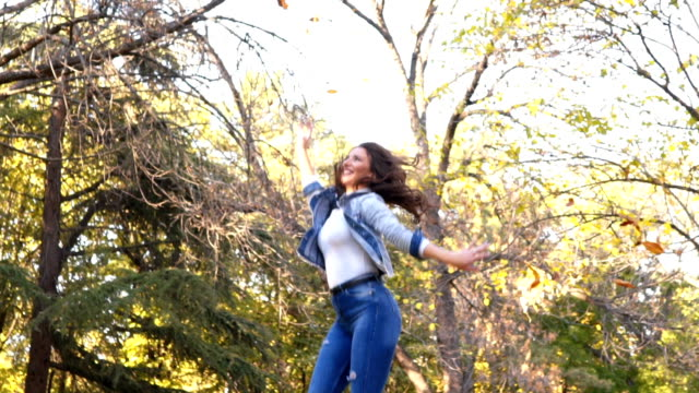 woman jumps and throws autumn leaves - leaf stock videos & royalty-free footage