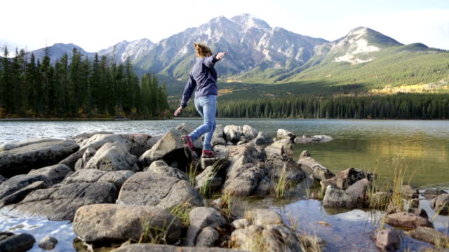 woman jumps rock to rock, arms outstretched - jasper national park stock videos & royalty-free footage