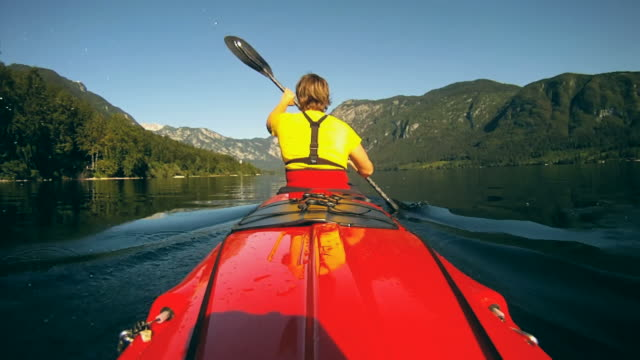 hd: donna kayak un lago. - kayak video stock e b–roll