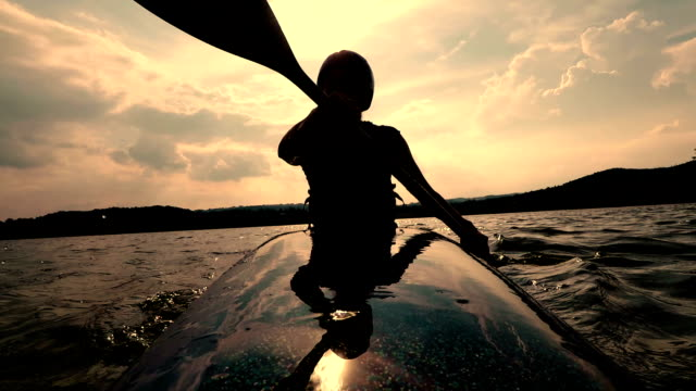woman kayaking at a calm lake during sunset - canoeing stock videos and b-roll footage