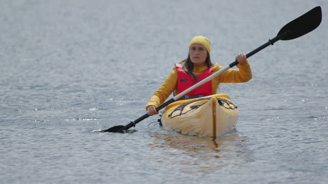 woman kayaking in mountain lake. paddling and eco tourism. - one mid adult woman only stock videos & royalty-free footage