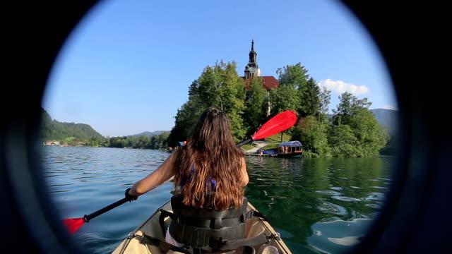 vídeos de stock e filmes b-roll de mulher caiaque no lago - lago bled