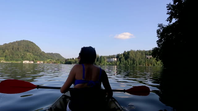 stockvideo's en b-roll-footage met vrouw kajakken in de lake - tourist