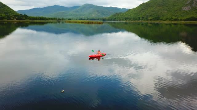 湖とタイで山にカヤックの女性 - カヤック点の映像素材/bロール